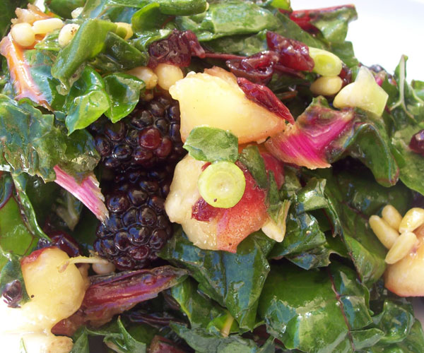 Kale and rainbow chard salad with peaches, blackberries & pinenuts